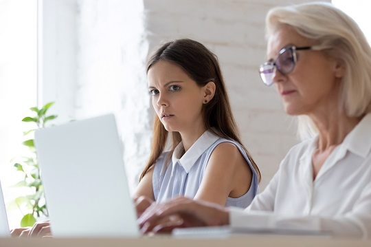 Young woman peeks at her employer's computer screen with suspicion.