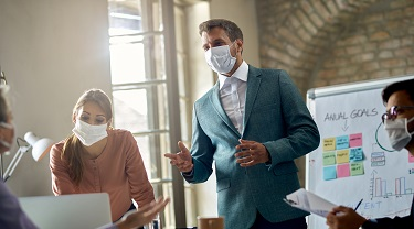 Male employer wearing a face mask explains corporate goals to his staff.