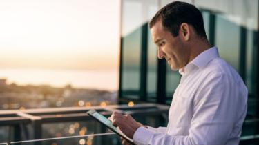 Exporter studies tablet on balcony looking over city skyline