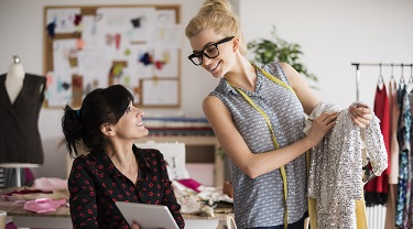 Two women entrepreneurs in the fashion clothing industry looking at their inventory of dresses