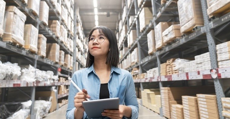 Young asian woman auditor in a warehouse looking up stock taking inventory on a computer tablet